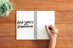 Foto plana de la opinión de la endecha del escritorio de trabajo con una escritura de la mano en la resolución del Año Nuevo en u Foto de archivo libre de regalías