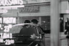 Foto preto e branco através da janela de pares bonitos novos que beijando no café fotografia de stock