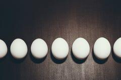 A foto preto e branco da linha dos ovos da páscoa brancos está no fundo preto com efeito do companheiro e no espaço para seu text Fotos de Stock Royalty Free