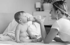 Foto preto e branco da mãe de sorriso que alimenta lhe 9 meses velha Imagem de Stock