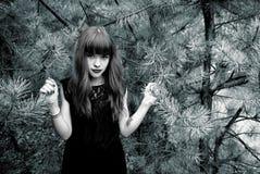 Foto preto e branco de uma menina bonita em um fundo do pinho Imagem de Stock