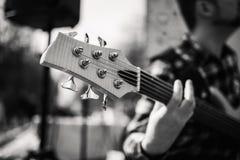 Foto preto e branco do playng do músico em seis guitarras-baixo fretless da corda na rua na frente dos povos imagens de stock royalty free