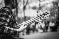 Foto preto e branco do playng do músico em seis guitarras-baixo fretless da corda na rua na frente dos povos fotografia de stock