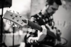 Foto preto e branco do playng do músico em seis guitarras-baixo fretless da corda na rua na frente dos povos foto de stock