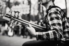 Foto preto e branco do playng do músico em seis guitarras-baixo fretless da corda na rua na frente dos povos fotos de stock royalty free