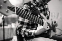 Foto preto e branco do playng do músico em seis guitarras-baixo fretless da corda na rua na frente dos povos foto de stock royalty free