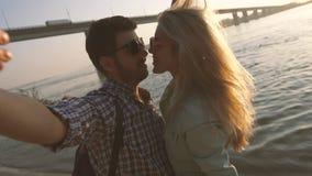 Foto que toma entera sonriente y que se besa de los pares apasionados de ellos mismos en la puesta del sol almacen de metraje de vídeo
