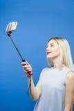Foto que toma rubia feliz usando el palillo de Selfie en fondo azul Muchacha linda en vestido que se fotografía por Smartphone Imagen de archivo
