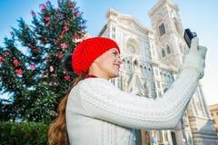 Foto que toma turística de la mujer cerca del árbol de navidad en Florencia Foto de archivo libre de regalías