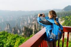 Foto que toma turística femenina de las montañas de Zhangjiajie, China Fotografía de archivo libre de regalías