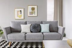 Foto real de um sofá cinzento com descansos preto e branco em um livi fotos de stock royalty free