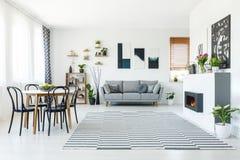 Foto real de um sofá cinzento que está na sala de visitas espaçoso com imagens de stock royalty free