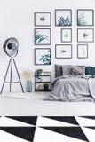 Foto real de uma cama que está ao lado de uma prateleira com plantas e um b imagem de stock