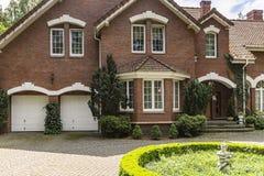Foto real de uma casa do tijolo com uma janela, as garagens e o redondo de baía fotos de stock