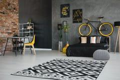 Foto real de un interior del dormitorio del ` s del adolescente con la cama negra, bici Foto de archivo libre de regalías