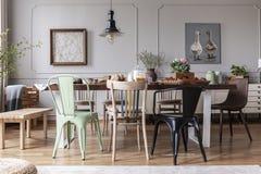 Foto real de un interior ecléctico del comedor con las diversas sillas en la tabla, la lámpara y la pintura con los patos imágenes de archivo libres de regalías