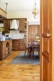Foto real de un interior de madera de la cocina con los armarios, cenando t foto de archivo