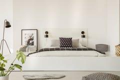 Foto real de una cama con las hojas blancas, la almohada negra y el bla gris Foto de archivo