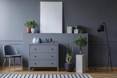 Foto real de una sala de estar monocromática con un pecho del cajón fotografía de archivo