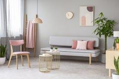 Foto real del salón con las almohadas rosadas sucias, cartel simple, perno imágenes de archivo libres de regalías
