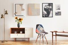 Foto reale dell'interno eclettico luminoso del salone con molti manifesti, sedia variopinta, armadietto di legno con i fiori e ta fotografie stock