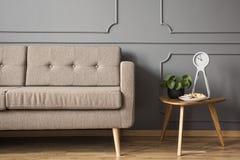 Foto reale di retro sofà che sta accanto ad una piccola tavola con la a immagini stock libere da diritti