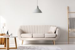 Foto reale di un sofà beige che sta in un inte semplice del salone fotografia stock libera da diritti