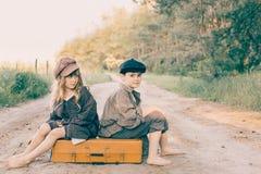 Foto retro de duas crianças com a grande mala de viagem amarela na estrada Fotografia de Stock