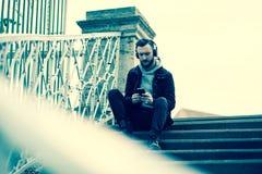 Foto retro do estilo de um homem do moderno que verifica seu telefone Fotografia de Stock