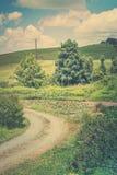 Foto retro do estilo de uma paisagem rural pastoral com a estrada do cascalho que enrola a lagoa passada do l?rio para Rolling Hi fotografia de stock royalty free