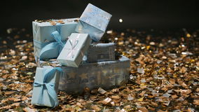 Foto`s blue box gifts and Golden confetti. On a black background stock video footage