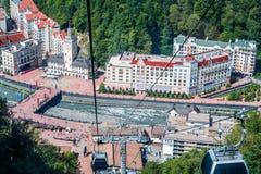 Foto's van gebouwen, kabelbaan, rivier bij voet bergen Stock Afbeelding