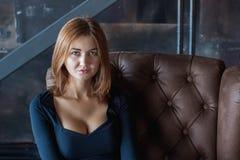 Foto's van mooie sensuele vrouwenzitting op een bank stock afbeelding
