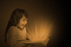 Foto scura del libro aperto della tenuta della bambina Immagine Stock