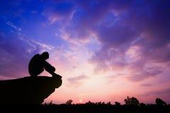 Foto silueteada Hombre solo que se sienta en el acantilado foto de archivo libre de regalías
