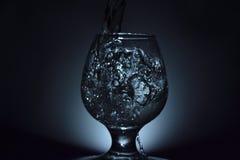 Foto simple de la aún-vida del vidrio del whisky, del chorro de agua y del colou oscuro Imagenes de archivo