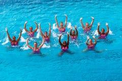 Foto sincronizada de la acción de la danza de las personas de nadada Foto de archivo