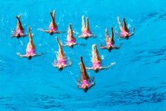 Foto sincronizada de la acción de la danza de las personas de nadada Fotos de archivo libres de regalías