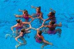 Foto sincronizada de la acción de la danza de las personas de nadada Fotografía de archivo libre de regalías