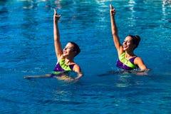 Foto sincronizada de la acción de la danza de los pares de las muchachas de la nadada Fotografía de archivo libre de regalías