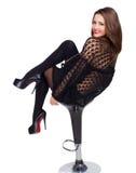 Foto som den härliga flickan i svart sitter på stolen Arkivfoto