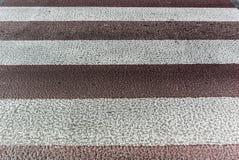 Foto som stiliseras som ett retro av den delvist urblekta vit-röda övergångsstället på asfalt royaltyfri fotografi