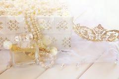 A foto sonhadora do branco peroliza a garrafa da colar, da tiara e de perfume Fotografia de Stock