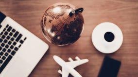 Foto sopraelevata dell'aeroplano, del computer portatile e del globo fotografia stock