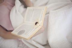 Foto suave de la mujer en cama con la opinión superior de la taza del libro y de café Imagen de archivo libre de regalías