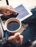 Foto suave de la mujer en la butaca con la tableta y la taza de café en las manos, vaqueros rasgados Foto de archivo