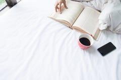 Foto suave de la mujer en la cama con el libro viejo y la taza del café a Fotografía de archivo libre de regalías