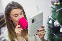 Foto suave de la mujer en la cama con la taza de libro de lectura del té Fotos de archivo libres de regalías