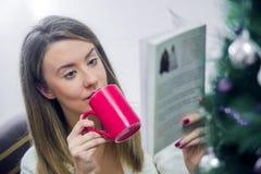 Foto suave de la mujer en la cama con la taza de libro de lectura del té Wom Imagen de archivo libre de regalías
