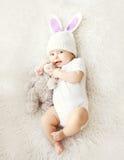 Foto suave del bebé lindo dulce en sombrero hecho punto con los oídos de un conejo Fotografía de archivo